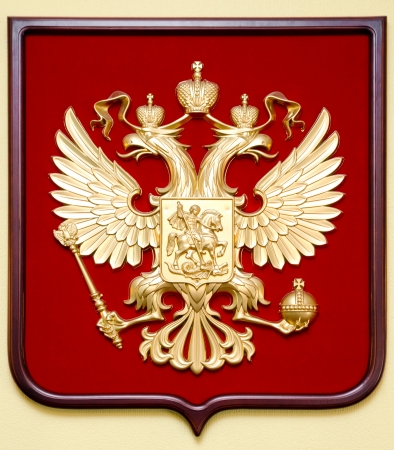 double headed eagle: the State Emblem of the Russian Federation - a golden double headed eagle on deep red