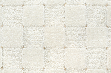 a woolen white carpet with a relief checked pattern photo