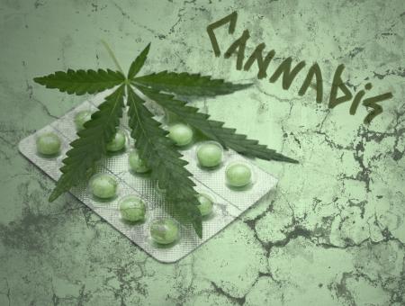medical  plant: una hoja de marihuana (Cannabis sativa) en un blister con las drogas verde - textura grunge