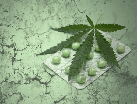 a leaf of marijuana (Cannabis sativa) on a blister with green drugs - grunge texture Stock Photo - 16233848