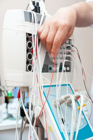 encephalon: rheoencephalography - a doctor connects wires of electrodes Stock Photo