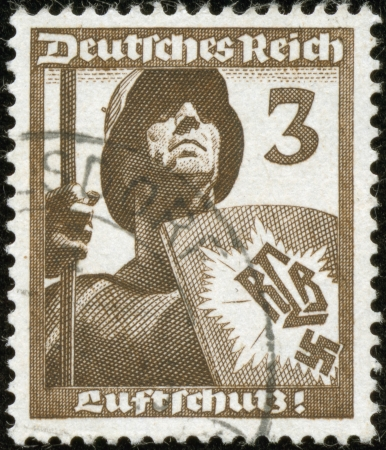 fascist: GERMANY - CIRCA 1937  A stamp printed by the fascist Germany Post is entitled  Luftshutz    Air defence  It shows a soldier in a helmet holding a shield with the letters RLB, circa 1937