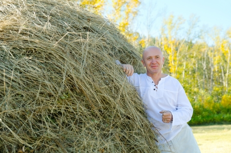 agreeable: a caucasian man in a white shirt rests against a haystack Stock Photo
