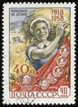 Communist: SOVIET UNION - CIRCA 1958  A stamp printed by the Soviet Union Post is entitled  Komsomol at virgin land   It shows a young woman holding a wheat bundle, circa 1958