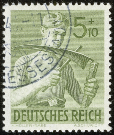 german fascist: GERMANY - CIRCA 1943  A stamp printed by the fascist Germany Post is entitled  German Empire   It shows a soldier whetting a scythe, circa 1943