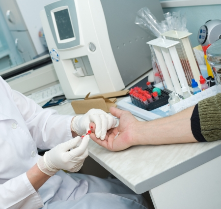 a nurse collects blood specimen from a finger Stock Photo - 16783269
