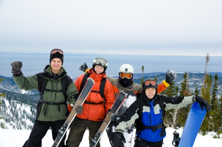 a group of snowboarders and skiers high in mountains photo