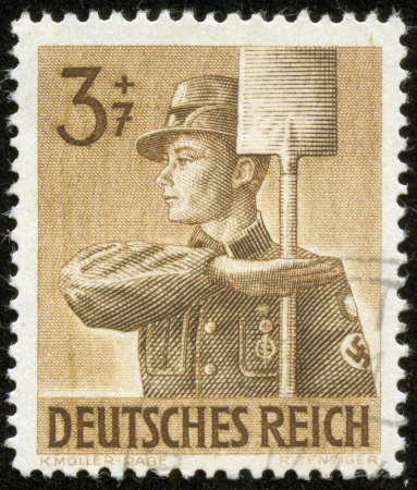 german soldier: GERMANY - CIRCA 1943  A stamp printed by the fascist Germany Post is entitled  German Empire   It shows a soldier holding a shovel, circa 1943