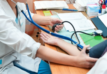 a doctor takes a patients blood pressure Stock Photo - 17179378