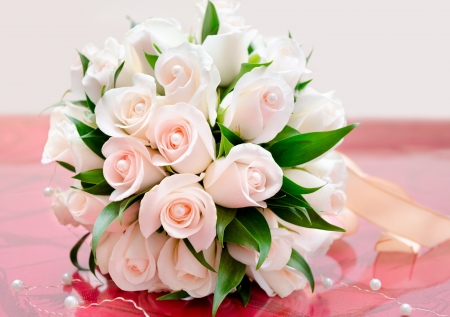 festive occasions: bridal bouquet of delicate light roses on red table Stock Photo
