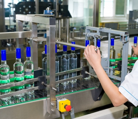 overseer: an operator monitors moving vodka bottles on conveyor