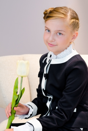 beautiful caucasian schoolgirl  11 years  smiles into camera holding tulip photo