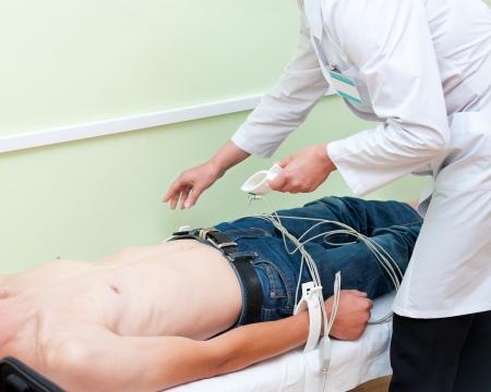 electrocardiograma: un médico fija sensores en un paciente para tomar su electrocardiograma