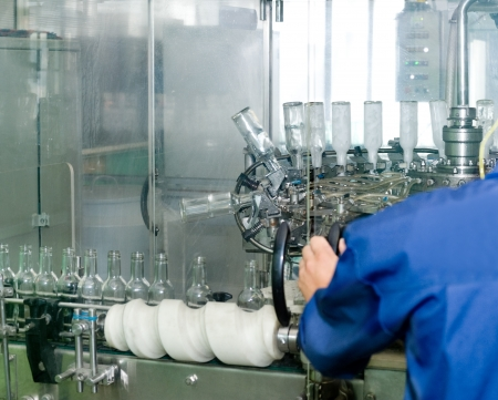 overseer: an operator monitors cleansing of vodka bottles on conveyor