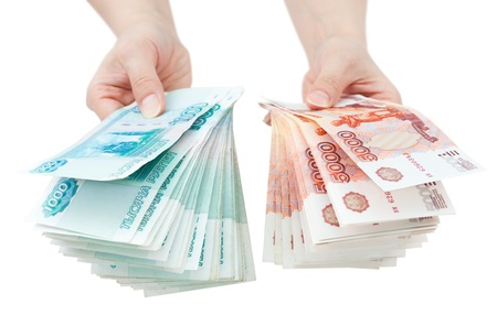 encash: two hands offer two batches of many 1000 and 5000 rouble bills  the biggest Russian bond