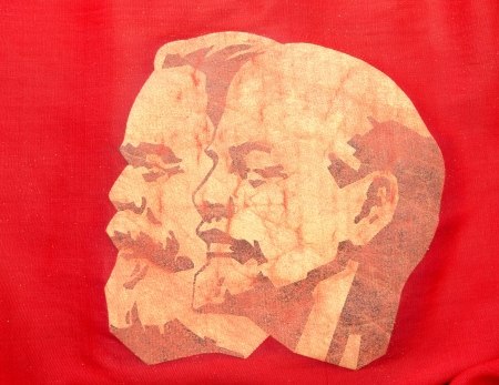 portraits of Karl Marx and Vladimir Lenin on red banner, closeup