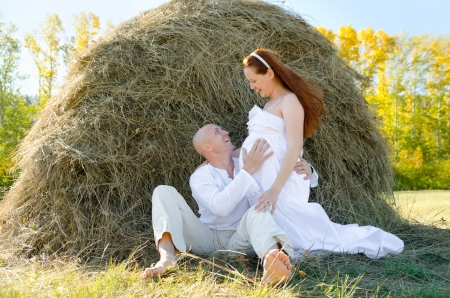happy married couple - husband hugs his pregnant wife photo