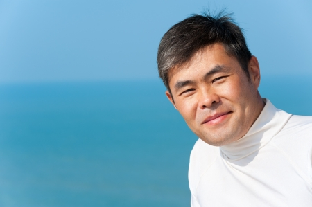 agreeable: handsome asian young man looks into camera smiling, blue sea and sky