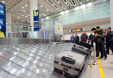 BEIJING - FEBRUARY 16  Unidentified air passengers wait for their baggage at Beijing airport luggage claim area, February 16, 2013 Beijing, China  報道画像
