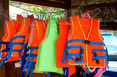 life jackets: orange life jackets for rent at hotel swimming pool Stock Photo