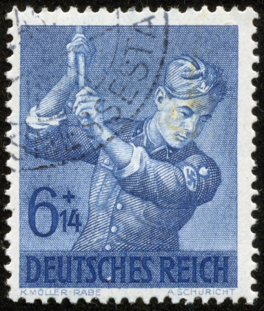 GERMANY - CIRCA 1943  A stamp printed by the fascist Germany Post is entitled  German Empire   It shows a soldier raising some tool, circa 1943 Stock Photo - 19369258
