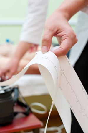 doctor makes electrocardiogram for patient, closeup shot