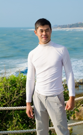 handsome asian young man looks into camera smiling, blue sea and sky Stock Photo - 19382715