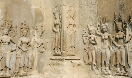 low relief in Angkor - female statues in crowns - Apsarases, female spirits of clouds and waters in Hindu and Buddhist mythology Stock Photo - 19382799