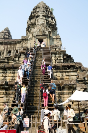 ANGKOR, CAMBODIA - FEB 20  Unidentified tourists climb to a praying tower at Angkor Wat  It is a part of the ancient Khmer complex Angkor, a UNESCO World Heritage Site, Feb 20, 2013, Angkor, Cambodia