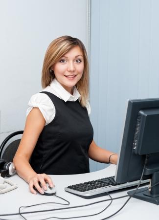 Mujer caucásica joven que se sienta delante de un ordenador mira a la cámara y sonríe