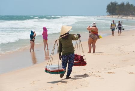 conical hat: a Vietnamese woman vendor carries food for sale, Mui Ne beach