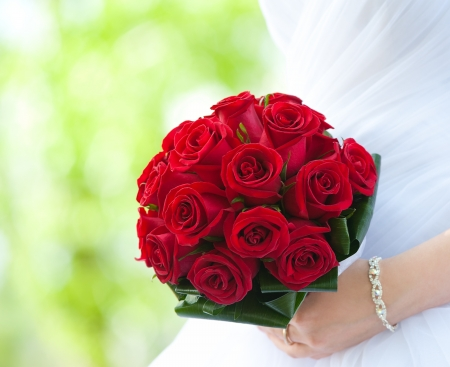 bride holds bouquet of red roses - summer green background photo