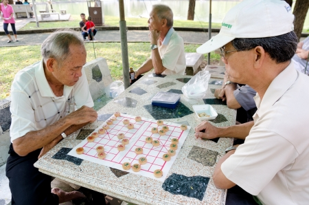BANGKOK, THAILAND - FEBRUARY 17: Unidentified local senior men spend spare time playing Chinese chess in the street, February 17, 2013, Bangkok, Thailand.
