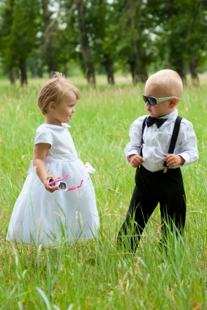 baby boy in sunglasses look at baby girl  both are dressed as bride and groom  photo