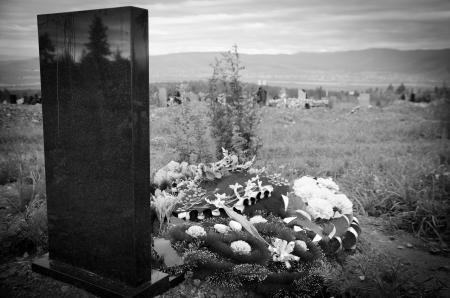 woe: black tomb with floral tributes, at cemetery