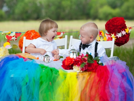 baby girl shouts at baby boy  both are dressed as groom and bride  photo