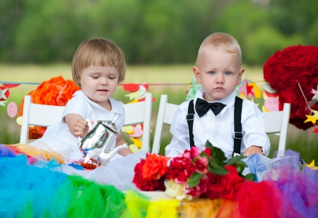 little girl and boy sit at festive table photo
