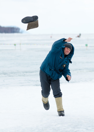 YARTSI, RUSSIA - APRIL 14  An unidentified man throws a valenok  felt boot , Apr 14, 2012, Yartsi, Buryatia, Russia  At annual Baikal Fishing Valenok Throwing was run