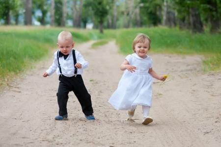 deux bébés - garçon et fille marche sur la route forestière