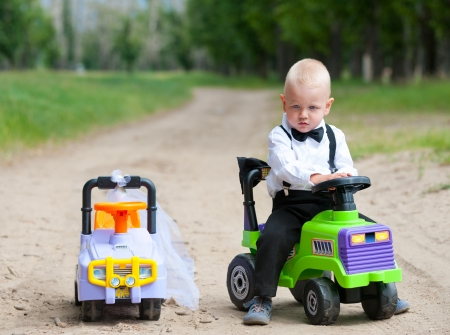 boys toys: sad baby boy at his toy car, another car beside is empty Stock Photo