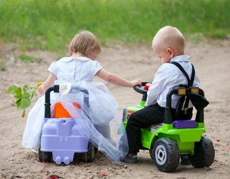 garçon et une fille habillée en mariée et le marié sont assis sur les voitures de jouets