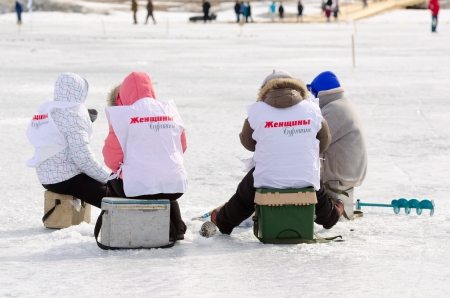 YARTSI, RUSSIA - APRIL 14  A team of fishers from the local political party Women of Buryatia sit around their ice hole during Baikal Fishing 2012, April 14, 2012 in Yartsi, Buryatia, Russia