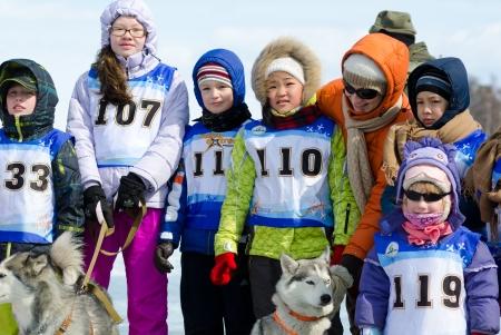 mushing: YARTSI, RUSSIA - APRIL 14  Unidentified children wait for their turn at annual Baikal Fishing where the 1st Mushing with husky dogs on inner tubes was run, Apr 14, 2012, Yartsi, Buryatia, Russia