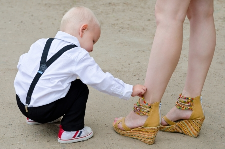 wedge: baby boy examines shoes on female legs Stock Photo