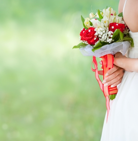 bride holds bouquet behind her back photo