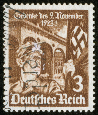 german soldier: GERMANY - CIRCA 1935  A stamp printed by the fascist Germany Post is entitled Do not forget November 23, 1923  It shows a soldier with a fascist banner, circa 1935