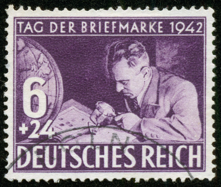 fascist: GERMANY - CIRCA 1942  A stamp printed by the fascist Germany Post is entitled Postage Stamp Day  It shows a stamp collector, circa 1942