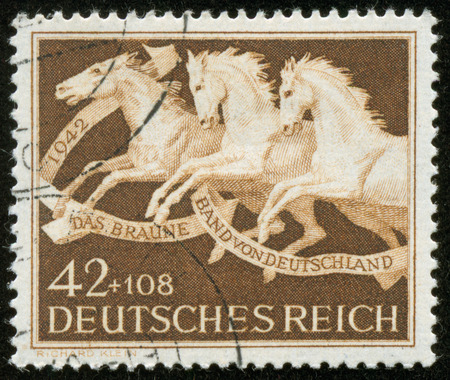 fascist: GERMANY - CIRCA 1942  A stamp printed by the fascist Germany Post is devoted to the 9th Horse Race  Brown Ribbon of Germany   It shows three running horses, circa 1942 Editorial