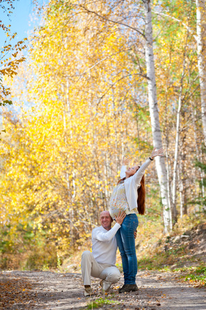 happy expectant parents - man holds his wife who lifted her face and arms towads the sky photo