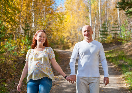 happy married couple - husband and his pregnant wife walk in autumn forest photo